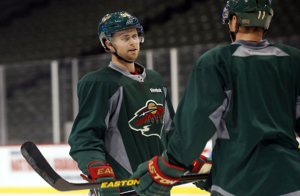 Minnesota Wild\'s Pierre-Marc Bouchard, left, chats with new teammate Zach Parise during NHL hockey practice, Tuesday, Jan. 15, 2013, in St. Paul, Minn. The canceled hockey games from the NHL lockout gave the Wild forward extra time to heal from his latest concussion, suffered more than a year ago. (AP Photo/Jim Mone)