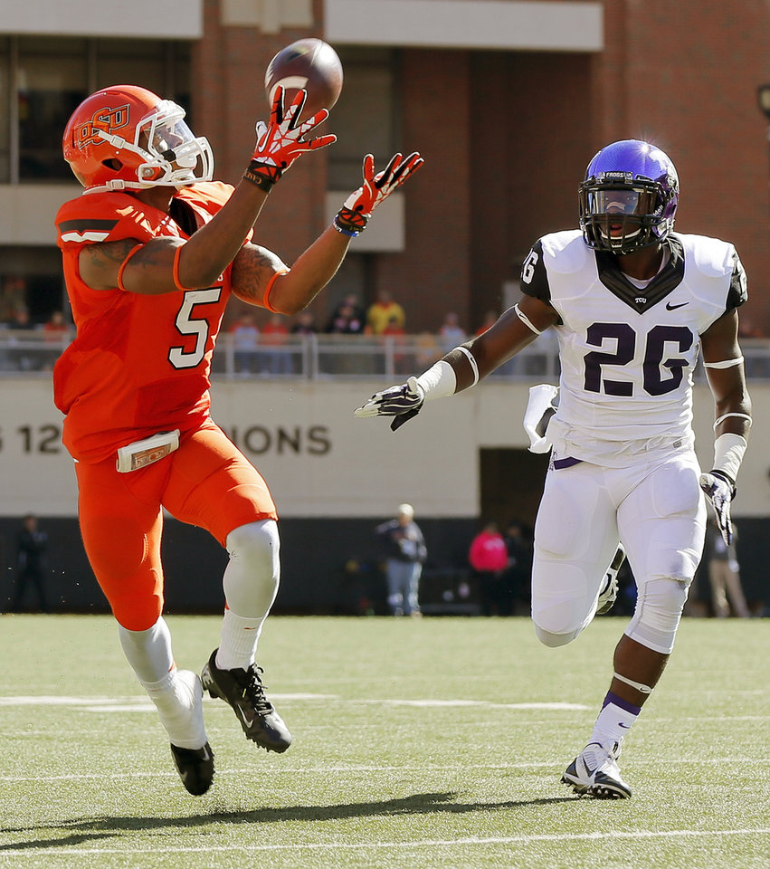 Oklahoma State's Josh Stewart (5) makes a catch in front of TCU's Derrick Kindred (26) in the second quarter during a college football game between the Oklahoma State University Cowboys (OSU) and the Texas Christian University Horned Frogs (TCU) at Boone Pickens Stadium in Stillwater, Okla., Saturday, Oct. 19, 2013. Photo by Nate Billings, The Oklahoman