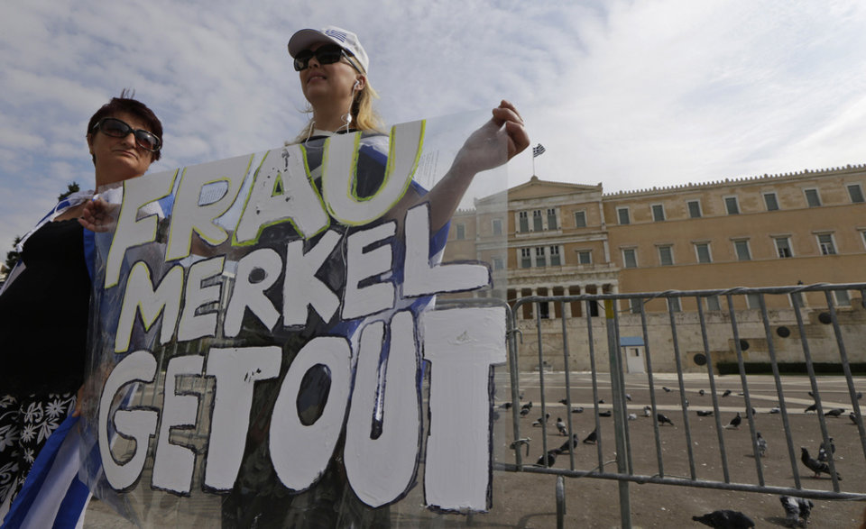 Photo -   Demonstrator holds an anti-Merkel banner prior to a protest in front of the Greek Parliament in Athens on Tuesday Oct. 9, 2012. German Chancellor Angela Merkel makes her first visit to Greece since the eurozone crisis began three years ago. Her five-hour stop is seen by the government as a historic boost for the country's future in Europe's shared currency, but by protesters as a harbinger of more austerity and hardship. More than 7,000 police will be on hand, cordoning off parks and other sections of central Athens, to keep demonstrators away from the German leader who is due to arrive Tuesday in the Greek capital for talks with conservative Prime Minister Antonis Samaras. (AP Photo/Lefteris Pitarakis)