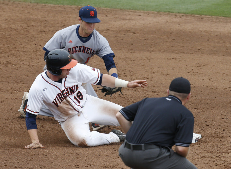Photo - Virginia catcher Nate Irving (18) makes it back to the bag as Bucknell infielder Greg Wasikowski (11) covers in the sixth inning during an NCAA College regional tournament baseball game in Charlottesville, Va., Friday, May 30, 2014. Virginia won the game 10-1. (AP Photo/Steve Helber)