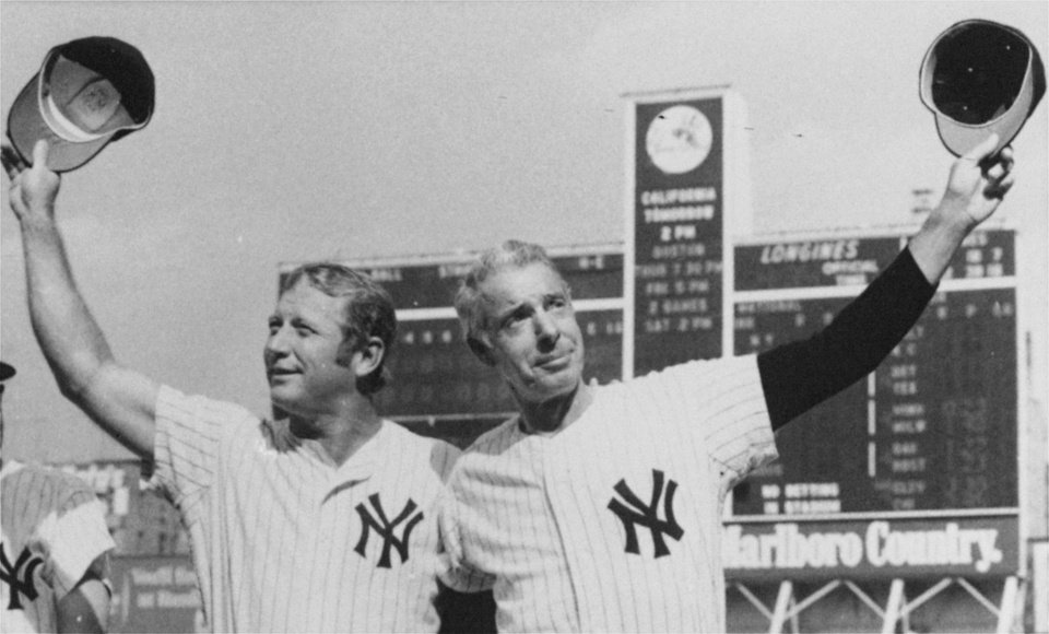 Photo - July 22, 1972 file photo, New York Yankee greats Mickey Mantle, left, and Joe DiMaggio, doff their caps to the crowd at Yankee Stadium as they appeared for an old timers game between games of a doubleheader between the Yankees and the California Angels. (AP Photo, File)