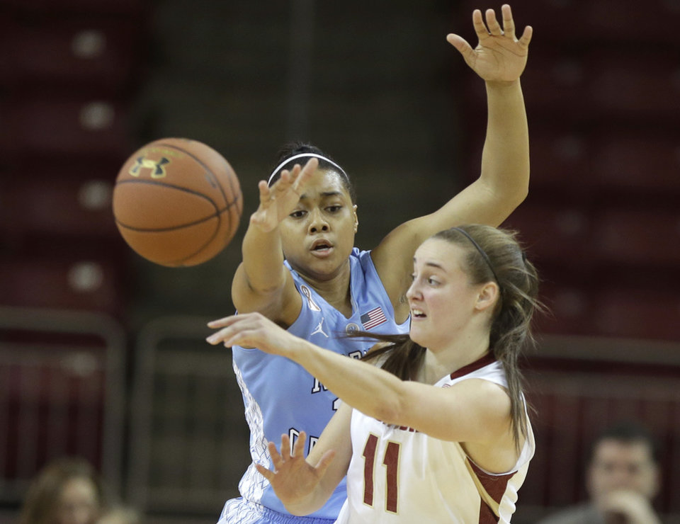 Photo - Boston College guard Nicole Boudreau (11) passes past North Carolina guard Allisha Gray, behind, in the first half of an NCAA college basketball game on Sunday, Jan. 19, 2014, in Boston. (AP Photo/Steven Senne)