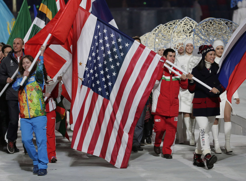 Photo - United States' Julie Chu, right,  carries her nation's flag while participating in the closing ceremony of the 2014 Winter Olympics, Sunday, Feb. 23, 2014, in Sochi, Russia. (AP Photo/Charlie Riedel)