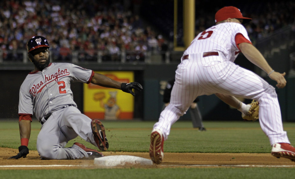 Photo - Washington Nationals' Denard Span, left, is safe at third before Philadelphia Phillies' Cody Asche can make the tag in the eighth inning of a baseball game on Friday, May 2, 2014, in Philadelphia. Washington won 5-3. (AP Photo/Laurence Kesterson)