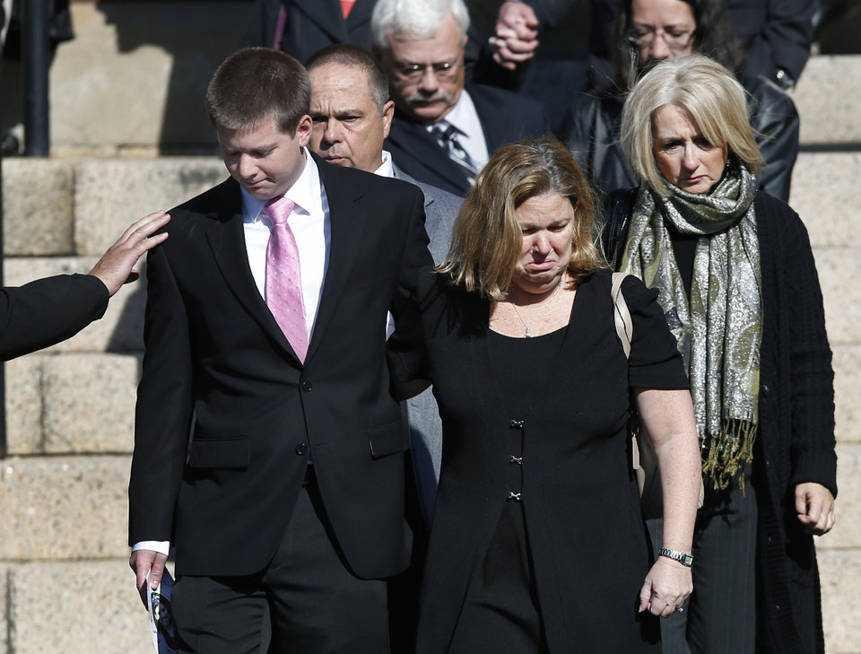 Photo - A mourner reaches out to Daniel Ritzer, brother of slain Danvers High School teacher Colleen Ritzer, as he accompanies his mother, Peggie, out of St. Augustine Church in Andover, Mass., Monday Oct. 28, 2013, after Colleen Ritzer's funeral service. Ritzer, 24, who taught math at Danvers High School, was killed in a school bathroom after dismissal Tuesday, police said. Her body was found in woods behind the school, and student Philip Chism, 14, has been arrested in connection with Ritzer's murder. (AP Photo/Elise Amendola)
