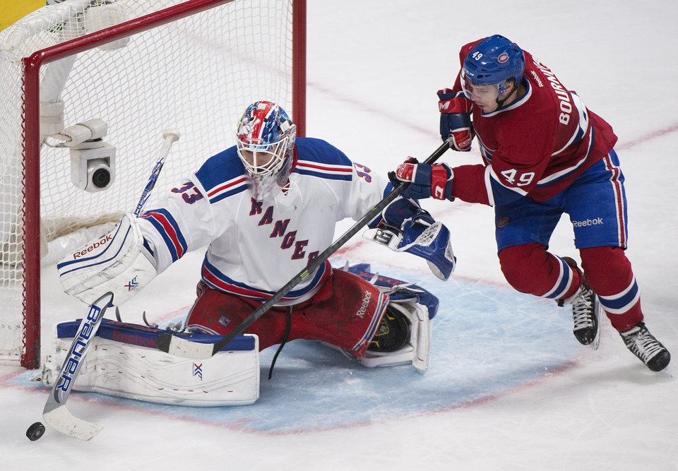 Photo - New York Rangers goaltender Cam Talbot makes a save against Montreal Canadiens' Michael Bournival, right, during the third period of an NHL hockey game, Saturday, April 12, 2014, in Montreal. Montreal won 1-0 in overtime. (AP Photo/The Canadian Press, Graham Hughes)