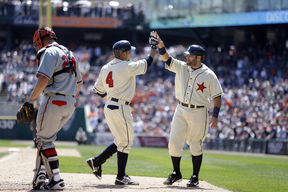 Detroit Tigers' Omar Infante (4) is greeted by teammate Alex Avila behind Atlanta Braves catcher Evan Gattis after Infante's home run during the fourth inning of an interleague baseball game in Detroit, Saturday, April 27, 2013. (AP Photo/Carlos Osorio)