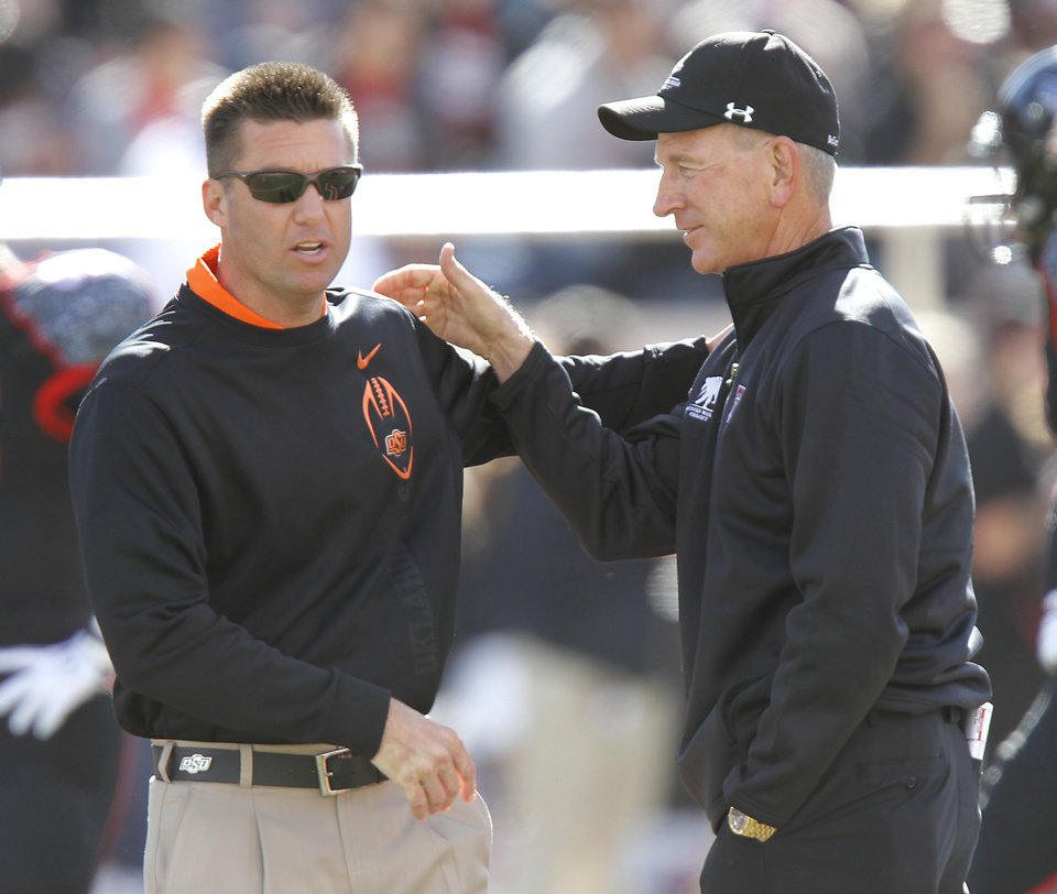 Photo - Oklahoma State coach Mike Gundy talks with Texas Tech coach Tommy Tuberville during the college football game between the Oklahoma State University Cowboys (OSU) and Texas Tech University Red Raiders (TTU) at Jones AT&T Stadium on Saturday, Nov. 12, 2011. in Lubbock, Texas.  Photo by Chris Landsberger, The Oklahoman