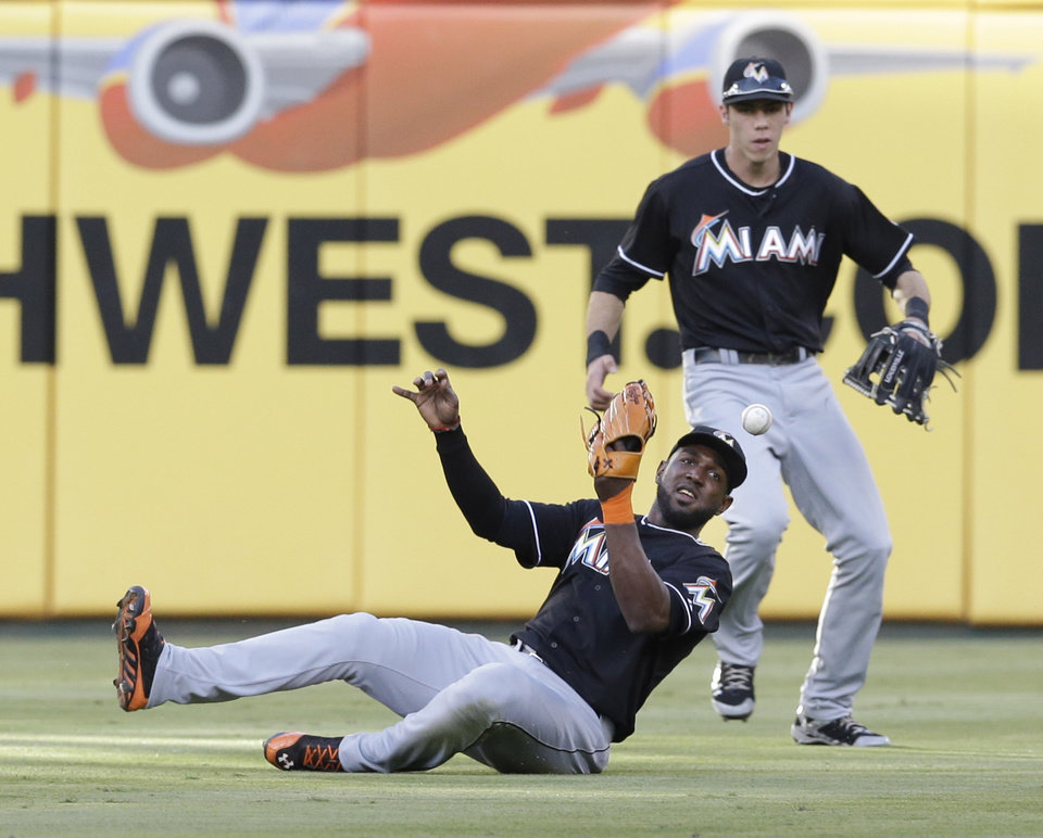 Photo - Miami Marlins center fielder Marcell Ozuna (13) can't handle the hit in front of teammate left fielder Christian Yelich giving up a single to Texas Rangers Alex Rios during the second inning of a baseball game in Arlington, Texas, Tuesday, June 10, 2014. (AP Photo/LM Otero)