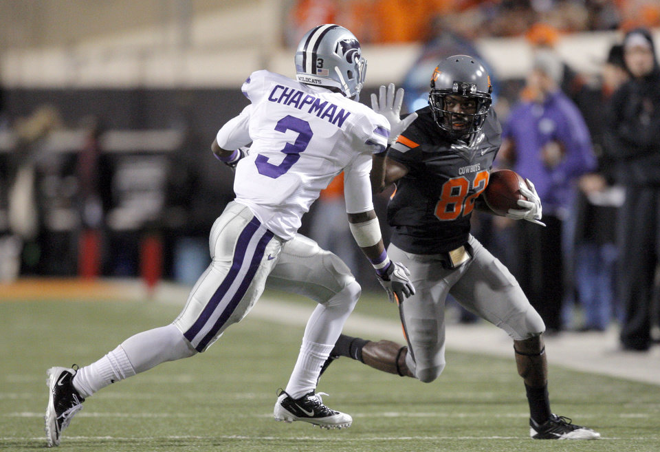 Photo - Oklahoma State's Isaiah Anderson (82) stiff arms Allen Chapman (3) during a college football game between the Oklahoma State University Cowboys (OSU) and the Kansas State University Wildcats (KSU) at Boone Pickens Stadium in Stillwater, Okla., Saturday, Nov. 5, 2011.  Photo by Sarah Phipps, The Oklahoman