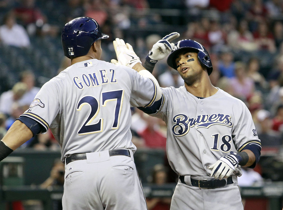 Photo - Milwaukee Brewers' Khris Davis (18) is congratulated after crossing home plate by teammate Carlos Gomez (27) following his three-run home run against the Arizona Diamondbacks during the fourth inning of a baseball game on Wednesday, June 18, 2014, in Phoenix. (AP Photo/Ralph Freso)
