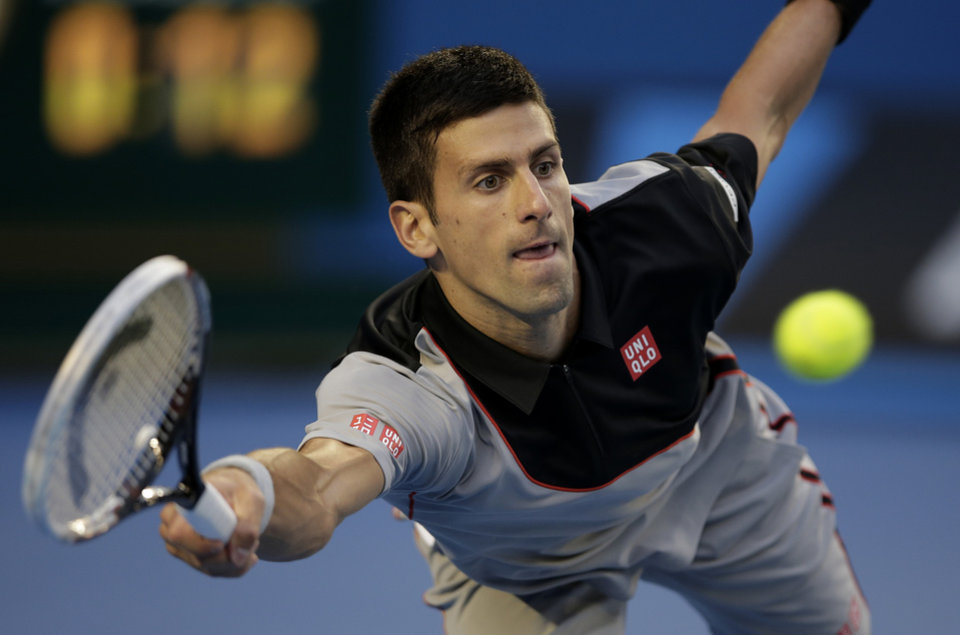 Photo - Novak Djokovic of Serbia makes a forehand return to Stanislas Wawrinka of Switzerland during their quarterfinal at the Australian Open tennis championship in Melbourne, Australia, Tuesday, Jan. 21, 2014.(AP Photo/Rick Rycroft)