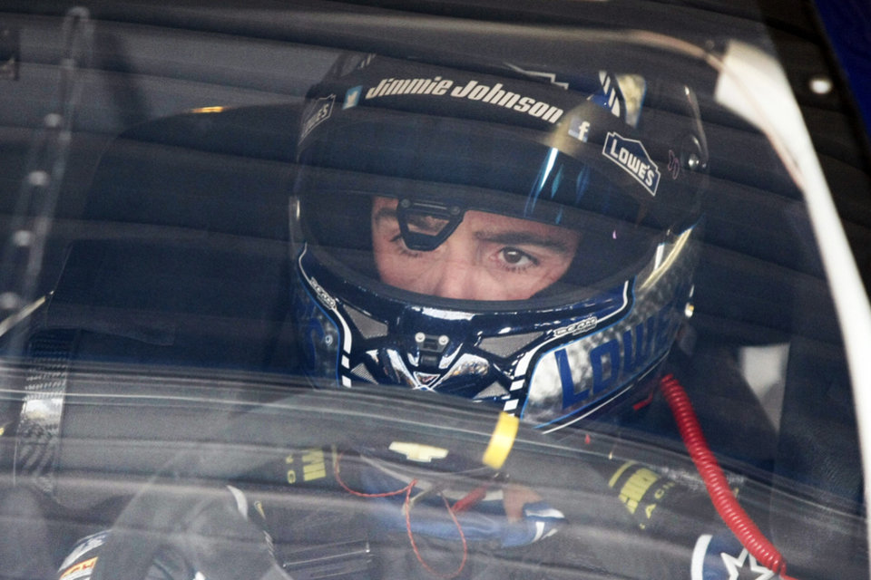 Photo - Driver Jimmie Johnson sits in his car before practice for Sunday's NASCAR Sprint Cup series auto race at Kansas Speedway in Kansas City, Kan., Friday, Oct. 4, 2013. AP Photo/Colin E. Braley)