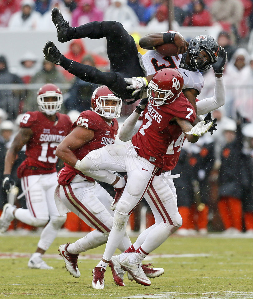 Photo - Oklahoma State's Chris Carson (32) leaps against Oklahoma's Jordan Thomas (7) in the second quarter during the Bedlam college football game between the Oklahoma Sooners (OU) and the Oklahoma State Cowboys (OSU) at Gaylord Family - Oklahoma Memorial Stadium in Norman, Okla., Saturday, Dec. 3, 2016. Photo by Nate Billings, The Oklahoman