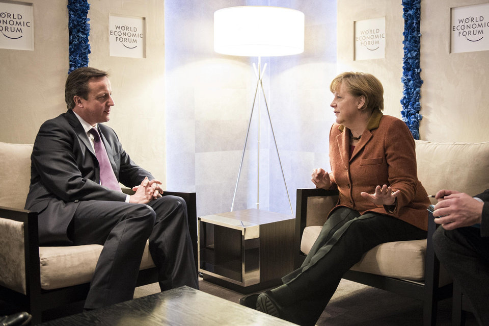 Photo - In this picture publicly provided by the German Government's Press Office, German chancellor Angela Merkel , right,  talks with British Prime Minister  David Cameron , during the World Economic Forum  in Davos, Switzerland, Thursday Jan. 24, 2013. (AP Photo/Jesco Denzel /Bundespresseamt)