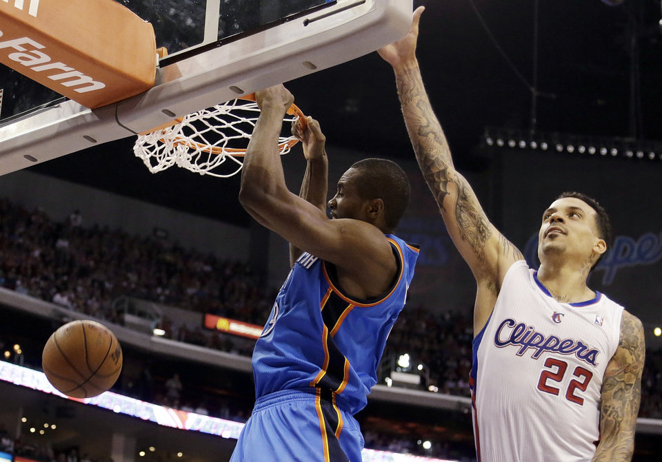 Photo - Oklahoma City Thunder forward Serge Ibaka (9), of the Republic of Congo, dunks as Los Angeles Clippers forward Matt Barnes (22) defends in the second half of an NBA basketball game in Los Angeles, Sunday, March 3, 2013. The Thunder won 108-104. (AP Photo/Reed Saxon)