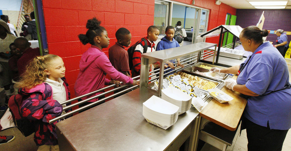 Photo - Cafeteria worker Vanessa Nicholson, far right, serving students breakfast at Millwood Elementary School in the Millwood Public School District in Oklahoma City Thursday, May 16, 2013. Photo by Paul B. Southerland, The Oklahoman