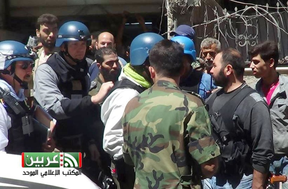 Photo - In this citizen journalism image provided by the United media office of Arbeen which has been authenticated based on its contents and other AP reporting, UN investigation team with blue helmets, speak with Syrian rebels, in Damascus countryside of Zamalka, Syria, Wednesday, Aug. 28, 2013. U.N. chemical weapons experts headed to a Damascus suburb on Wednesday for a new tour of areas struck by a purported poison gas attack, activists said, as Western powers laid the groundwork for a possible punitive strike and the U.N. chief pleaded for more time for diplomacy. (AP Photo/United media office of Arbeen)