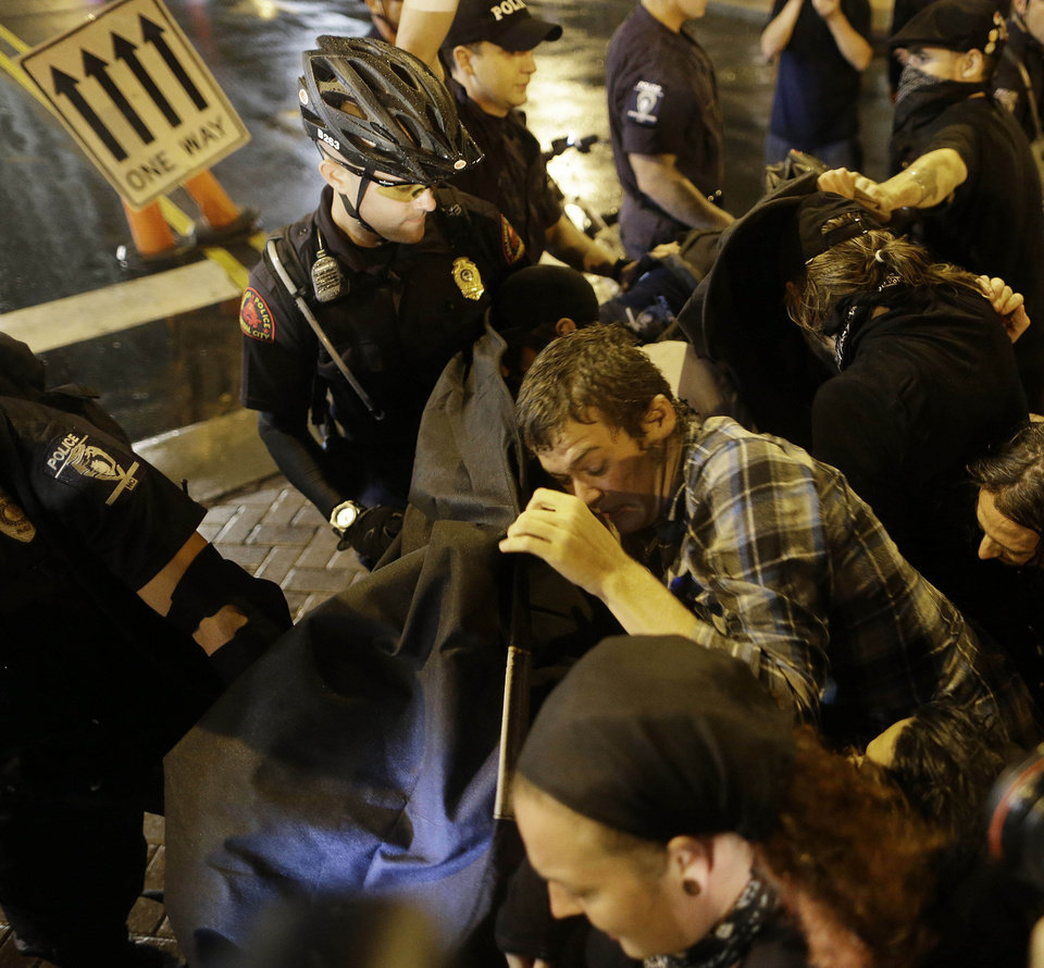 Photo - Occupy Demonstrators use a tarp to push against a police barricade during an unscheduled protest march, Tuesday, Sept. 4, 2012, in Charlotte, N.C. The Democratic National Convention begins today. (AP Photo/Patrick Semansky) ORG XMIT: XDNC160
