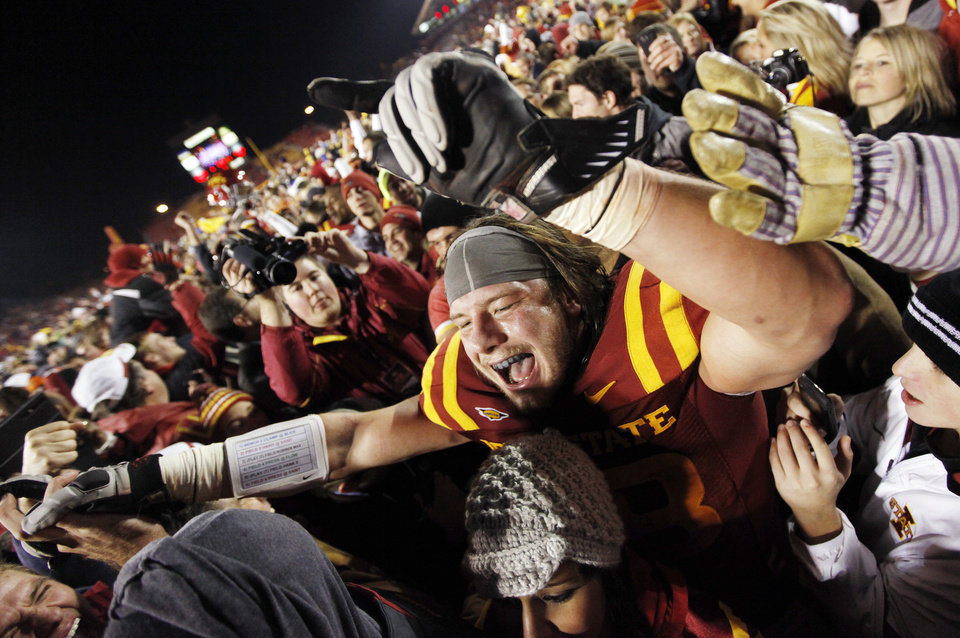 Photo - CELEBRATION: ISU's Jake Lattimer (48) celebrates with fans after a college football game between the Oklahoma State University Cowboys (OSU) and the Iowa State University Cyclones (ISU) at Jack Trice Stadium in Ames, Iowa, Friday, Nov. 18, 2011. Iowa State won, 37-31, in double overtime. Photo by Nate Billings, The Oklahoman