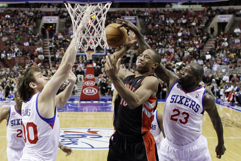 Toronto Raptors' DeMar DeRozan, center, cannot get a shot past Philadelphia 76ers' Spencer Hawes, left, and Jason Richardson in the first half of an NBA basketball game, Tuesday, Nov. 20, 2012, in Philadelphia. (AP Photo/Matt Slocum)