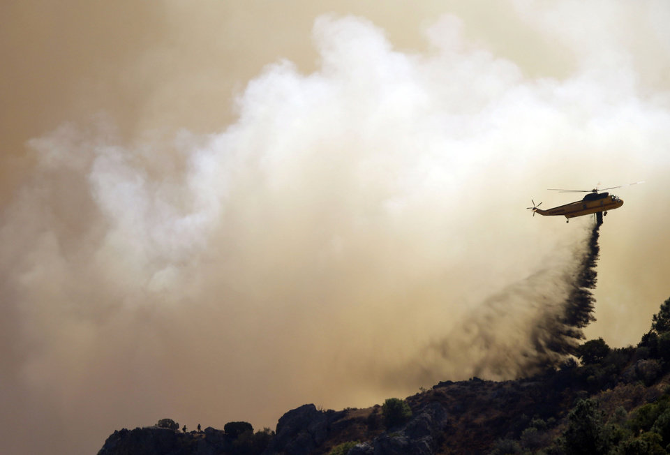 Photo - A helicopter drops retardant on a raging wildfire in Mount Diablo State Park in Contra Costa County, Calif. on Monday, Sept. 9, 2013. A wildfire burning outside Mount Diablo State Park has forced dozens of residents and animals to evacuate Monday. (AP Photo/Marcio Jose Sanchez)