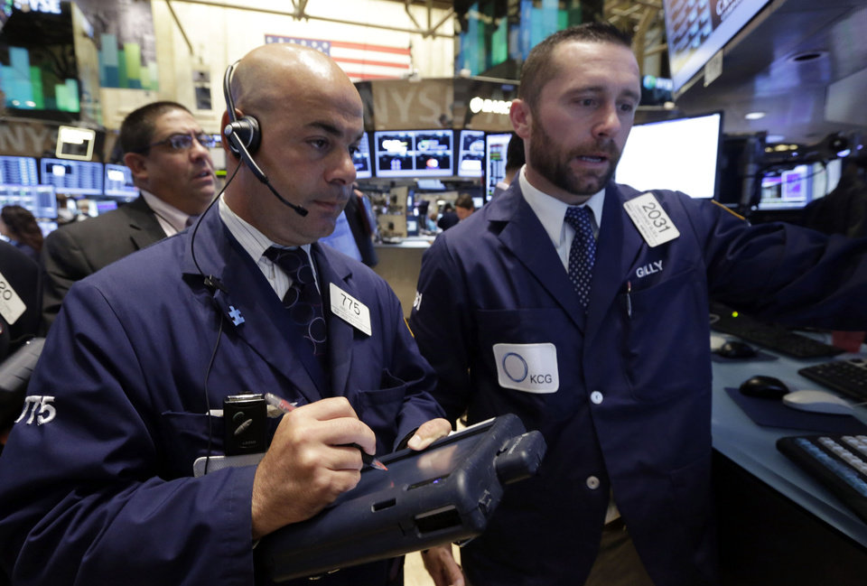 Photo - Trader Fred DeMarco, center, and specialist Christopher Gildea, right, on the floor of the New York Stock Exchange Monday, July 22, 2013. The stock market edged higher as a big week of earnings kicked off Monday, with mixed results from a handful of large U.S. companies. (AP Photo/Richard Drew)