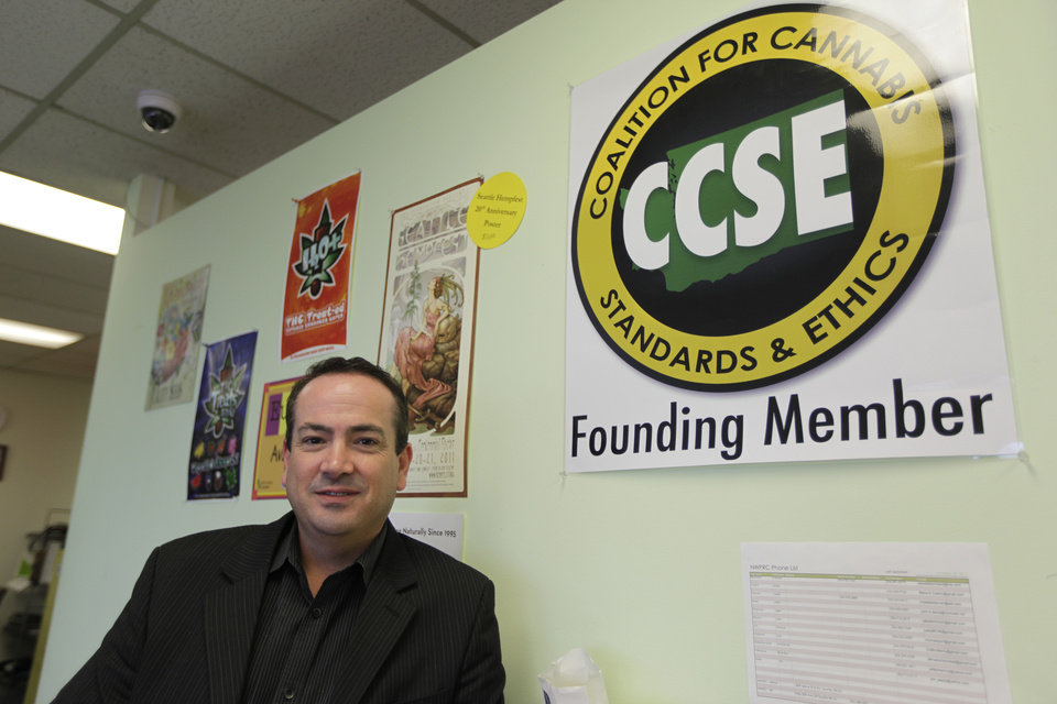 John Davis, chairman of the Coalition for Cannabis Standards and Ethics self-regulating trade organization, and co-owner of the Northwest Patient Resource Center medical marijuana dispensary, poses for a photo next to the CCSE certification logo, Wednesday, Nov. 7, 2012, at his dispensary in Seattle. After voters weighed in on election day, Colorado and Washington became the first states to allow pot for recreational use, but they are likely to face resistance from federal drug warriors. Davis, who says it would make sense for his business to evolve from serving medical patients to the general public, says that the CCSE has offered to work with Washington state regulators to help them develop policy and legal guidelines relating to the legal use of marijuana. (AP Photo/Ted S. Warren)