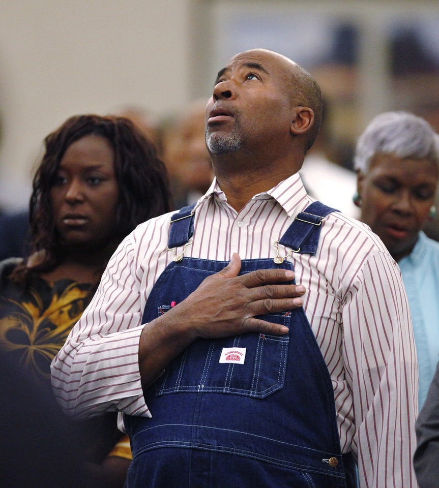 Photo - A man stands and covers his heart during the singing of the national anthem at the 16th annual Midwest City Dr. Martin Luther King, Jr. Prayer Breakfast inside the Reed Conference Center Monday morning, Jan. 21, 2013. The theme of this year's event is