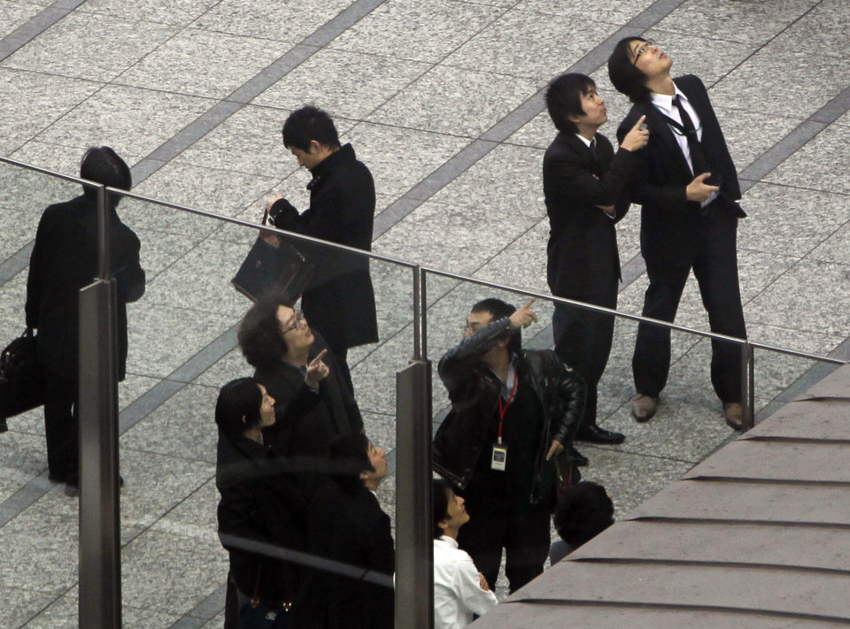 Photo - Office workers in Tokyo's Shiodome district near Tokyo Bay stay on the pedestrian deck, observing surrounding high-rise office and hotel buildings swaying Friday, March 11, 2011, shortly after a 7.9-magnitude earthquake has struck off Japan's northeastern coast. (AP Photo/Koji Sasahara) ORG XMIT: TOK107