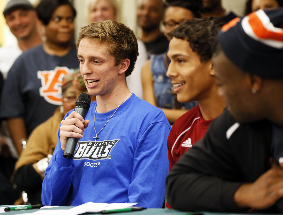 Photo - Austin Place, left, speaks during the signing day ceremony at Edmond Santa Fe High School in Edmond, Okla., Wednesday, Feb. 6, 2013. Next to Place are Matthew Giudice, middle, and Khari Harding. Place will play soccer for the University at Buffalo. Giudice will play soccer and run track for Hastings College. Harding will play football for Auburn. Photo by Nate Billings, The Oklahoman