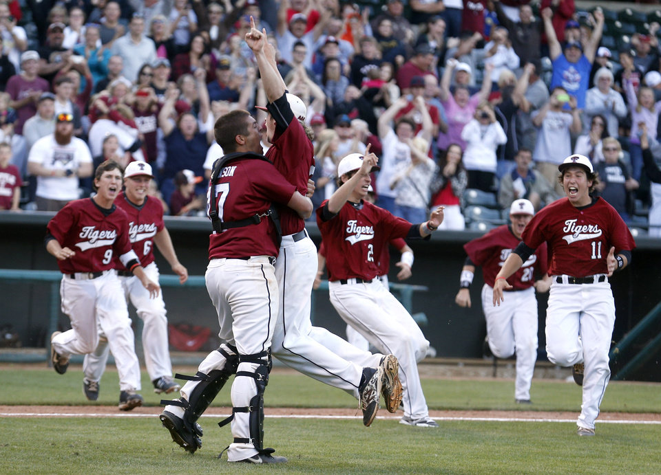 Photo - Tuttle's Connor Litterell, right, and Wyatt Johnson celebrate their class 4A state baseball championship over Dewey at the Chickasaw Bricktown Ballpark in Oklahoma City, Saturday, May 17, 2014. Photo by Sarah Phipps, The Oklahoman