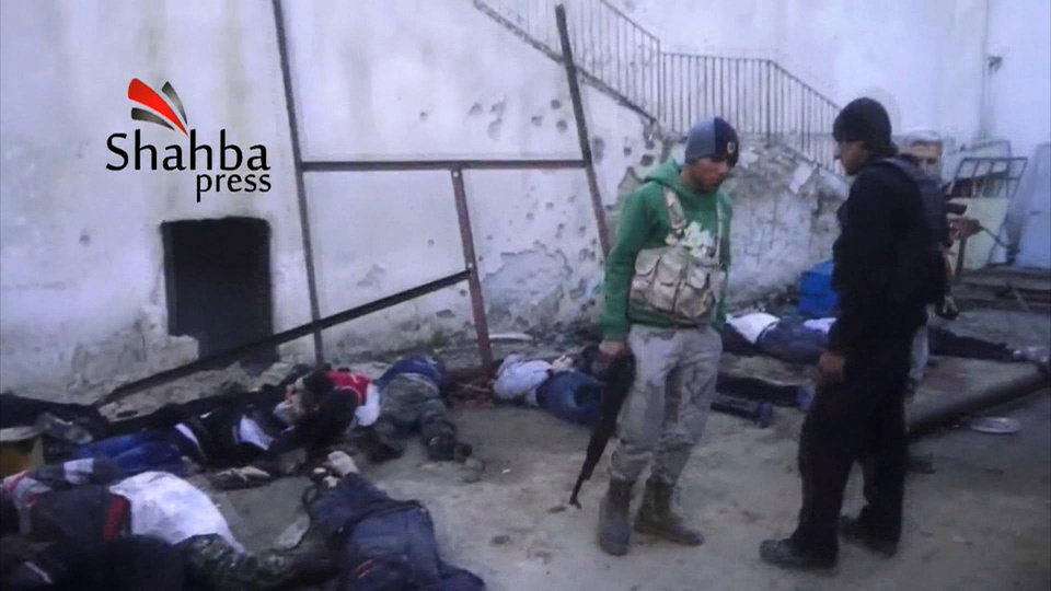 Photo - This image made from citizen journalist video posted by the Shahba Press on Wednesday, Jan. 8, 2014, which has been verified and is consistent with other AP reporting, shows rebel fighters standing next to dead bodies after they ousted Islamic State of Iraq and the Levant (ISIL) from their headquarters in a hospital in the Syrian city of Aleppo. Activists said the people were killed by fighters from the al-Qaida affiliate, which is trying to build Islamic rule across Syria. Rebel-on-rebel fighting between the al-Qaida-linked group and an array of more moderate and ultraconservative Islamists has killed nearly 500 people over the past week in northern Syria, an activist group said Friday, in the most serious bout of violence among opponents of President Bashar Assad since the civil war began. (AP Photo/Shahba Press via AP video)