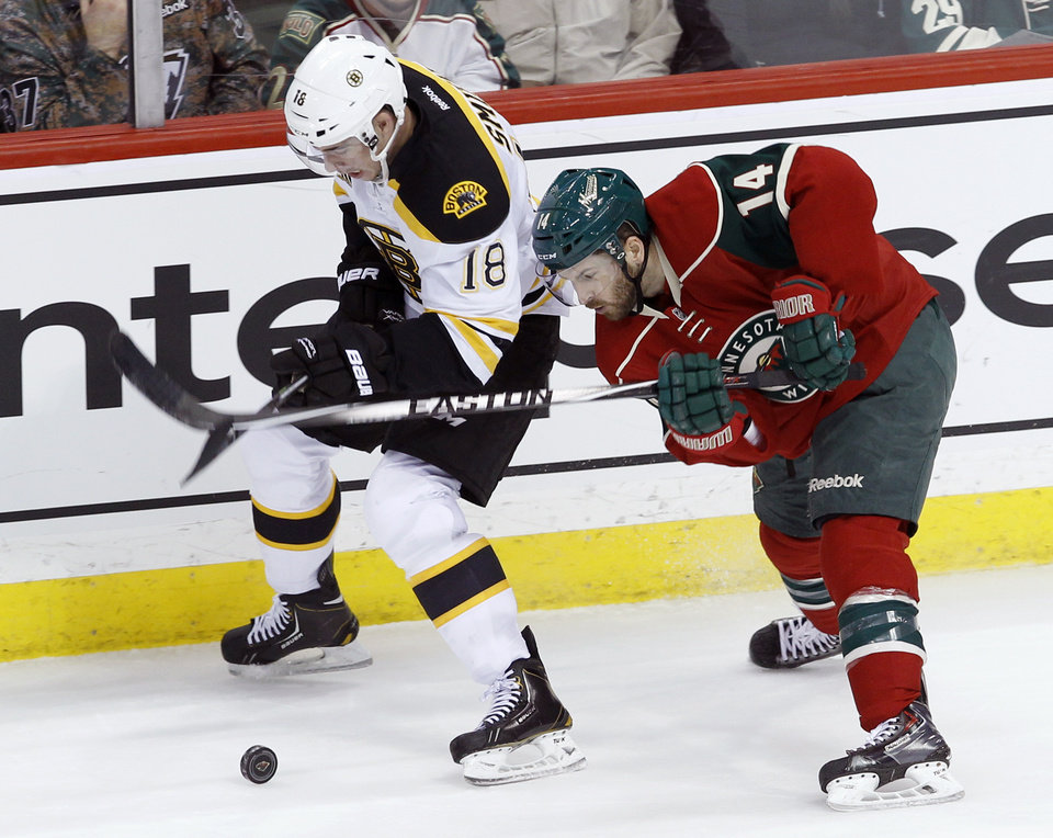 Photo - Boston Bruins right wing Reilly Smith (18) and Minnesota Wild right wing Justin Fontaine (14) chase the puck during the first period of an NHL hockey game in St. Paul, Minn., Tuesday, April 8, 2014. (AP Photo/Ann Heisenfelt)