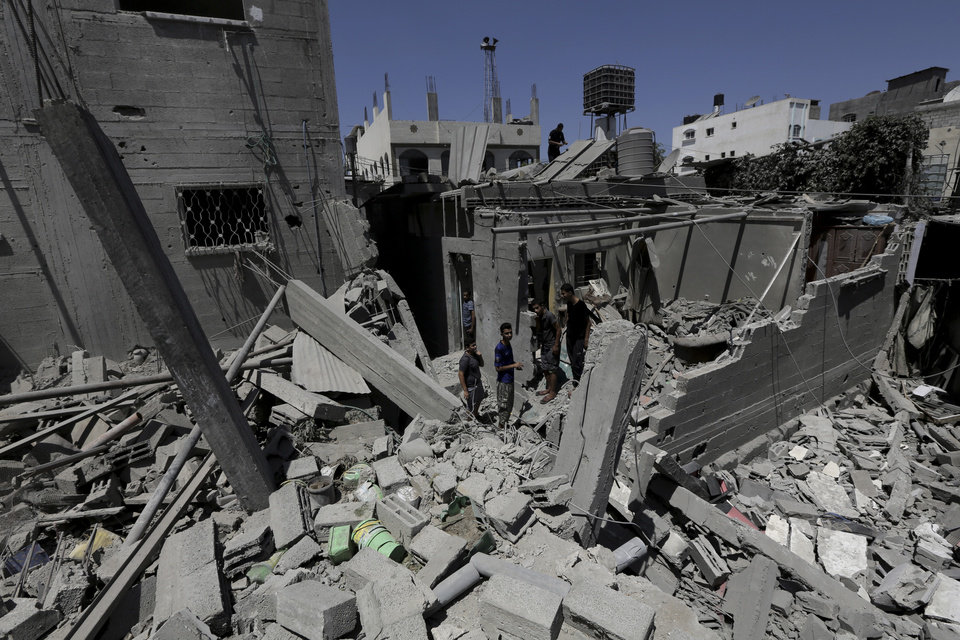 Photo - Palestinians, who are neighbors of a house belonging to Abu Hamada family, inspect the damage to their houses, after an Israeli strike in Jebaliya refugee camp, in the northern Gaza Strip, Monday, Aug. 25, 2014. Fifteen people were wounded in an airstrike on houses in Jebaliya refugee camp, according toGaza health official Ashraf al-Kidra. (AP Photo/Adel Hana)