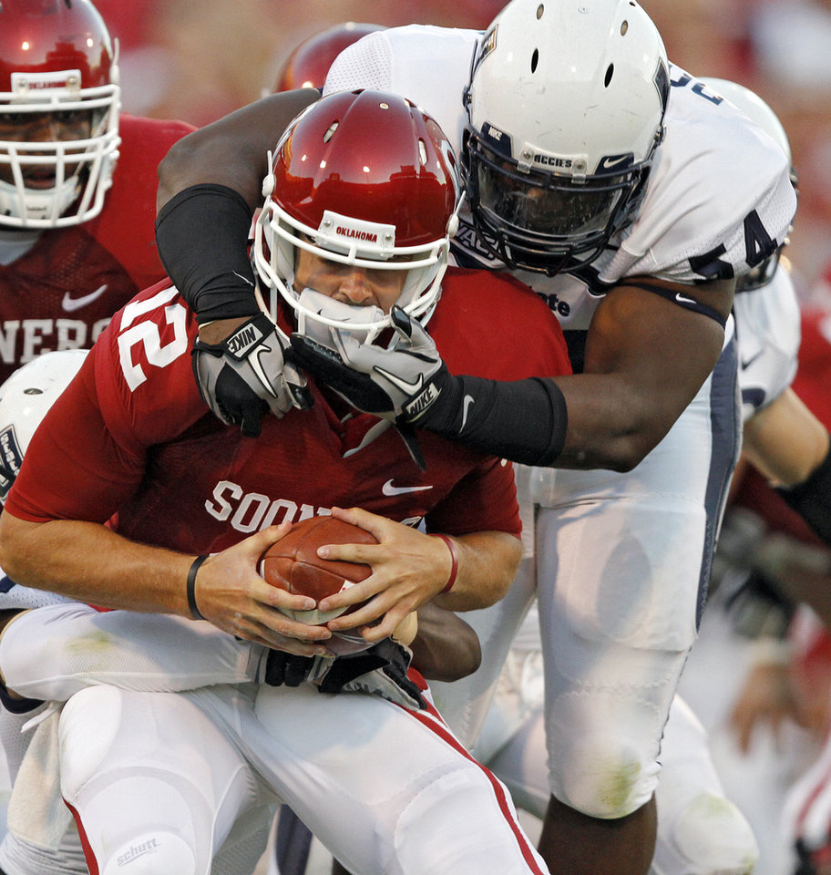 Photo - Oklahoma's Landry Jones (12) is sacked by Utah State's Nathan Royster (54) during the first half of the college football game between the University of Oklahoma Sooners (OU) and Utah State University Aggies (USU) at the Gaylord Family-Oklahoma Memorial Stadium on Saturday, Sept. 4, 2010, in Norman, Okla.   Photo by Chris Landsberger, The Oklahoman