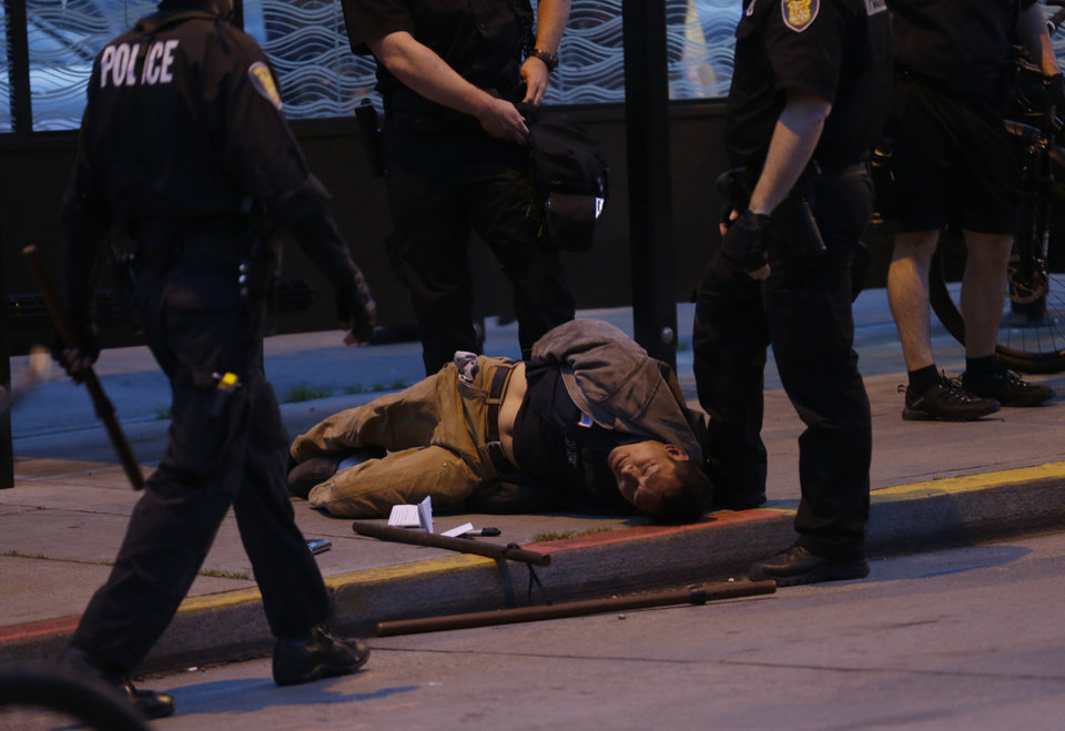 Photo - A protester who was arrested during a May Day march that began as an anti-capitalism protest and turned into demonstrators clashing with police lies on the ground next to police batons, Wednesday, May 1, 2013, in downtown Seattle. (AP Photo/Ted S. Warren)