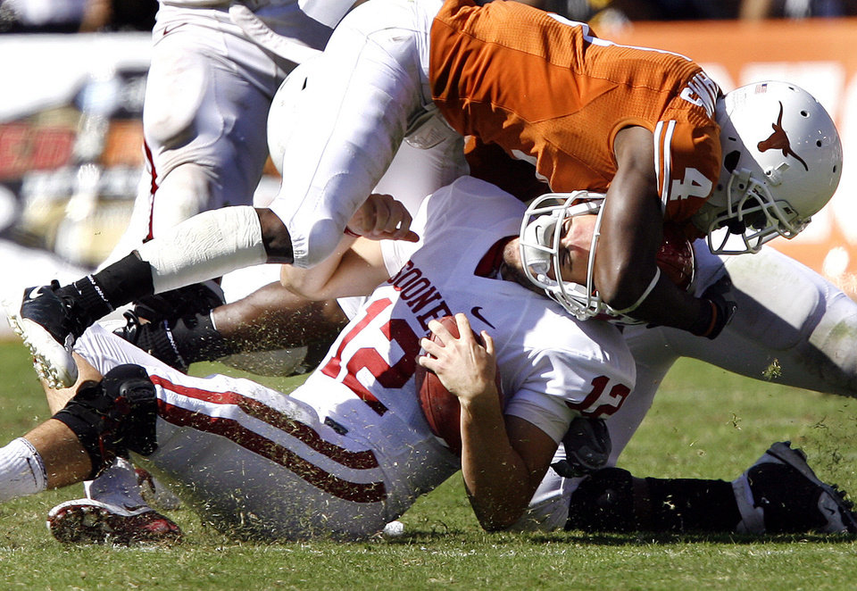 Photo - Oklahoma's Landry Jones (12) is hit by Texas' Aaron Williams (4) during the Red River Rivalry college football game between the University of Oklahoma Sooners (OU) and the University of Texas Longhorns (UT) at the Cotton Bowl in Dallas, Texas, Saturday, Oct. 17, 2009. Photo by Chris Landsberger, The Oklahoman