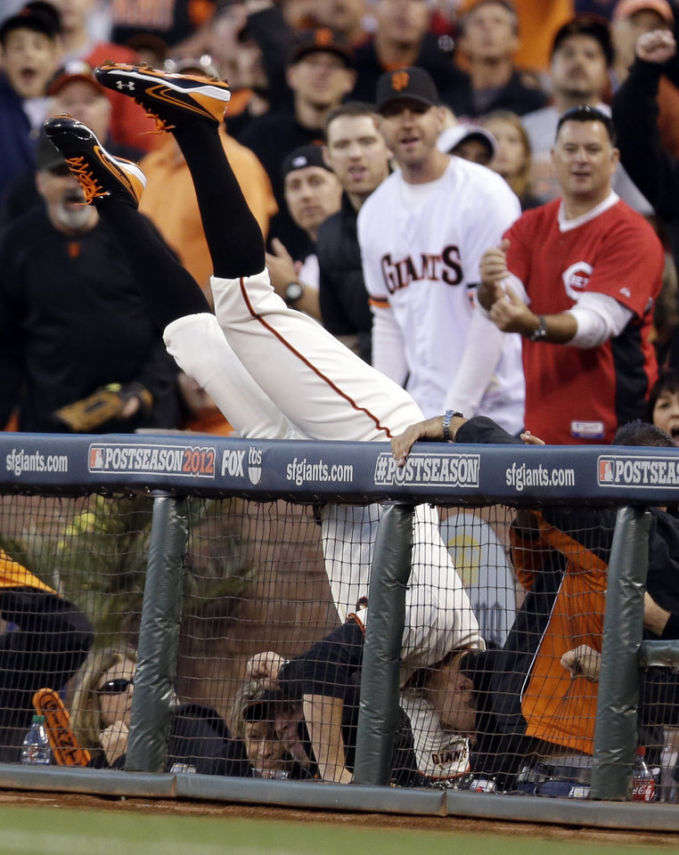 San Francisco Giants first baseman Brandon Belt makes a diving catch into the stands on a ball hit by Cincinnati Reds' Zack Cozart in the first inning of Game 1 of the National League division baseball series in San Francisco, Saturday, Oct. 6, 2012. (AP Photo/Marcio Jose Sanchez)