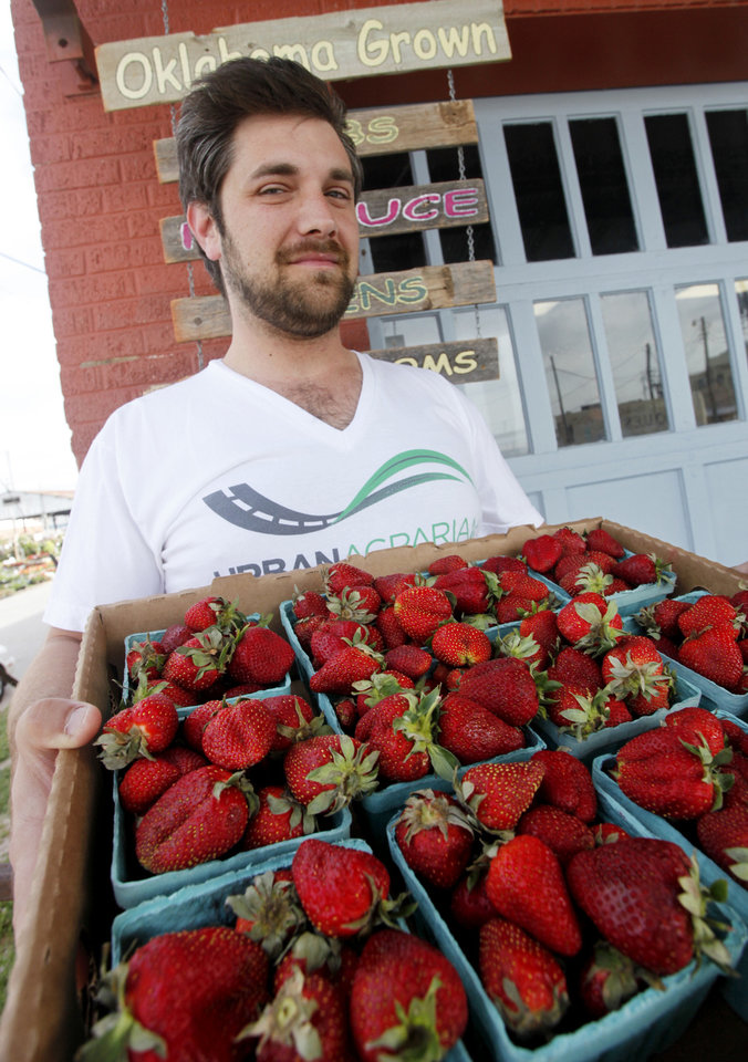 Matthew Burch, of the Urban Agrarian, with a flat of local strawberries. <strong>DOUG HOKE - THE OKLAHOMAN</strong>