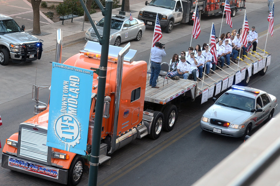 FILE - In this Nov. 15, 2012 file photo, a flatbed truck carries wounded veterans and their families during a parade before it was struck by a train in Midland, Texas. A 50-year-old Army veteran who served in Iraq and Afghanistan was driving the parade float that investigators say edged across a railroad crossing in Texas despite warning signals of a fast approaching train, the man's attorney said Tuesday, Nov. 20, 2012. Four veterans and sixteen people were injured in the resulting collision. (AP Photo/Reporter-Telegram, James Durbin, File)