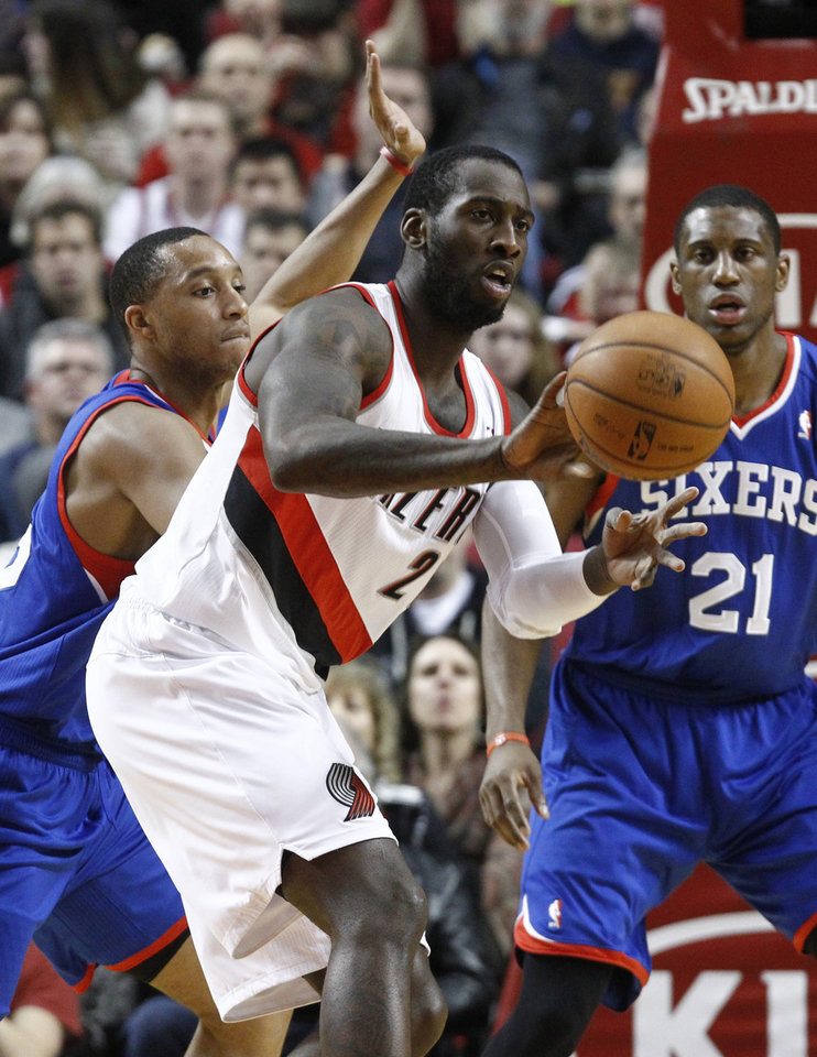 Portland Trail Blazers center J.J. Hickson, middle, flips the ball out against the defense of the Philadelphia 76ers Thaddeus Young, right, and Evan Turner during the first quarter of an NBA basketball game in Portland, Ore., Saturday, Dec. 29, 2012.(AP Photo/Don Ryan)