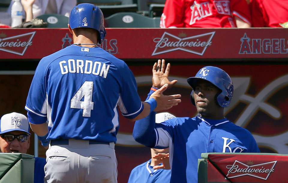Photo - Kansas City Royals' Alex Gordon (4) gets a high-five from teammate Edinson Rincon, right, after Gordon scored a run against the Los Angeles Angels during the first inning of a spring training baseball game Friday, March 21, 2014, in Tempe, Ariz. (AP Photo/Ross D. Franklin)