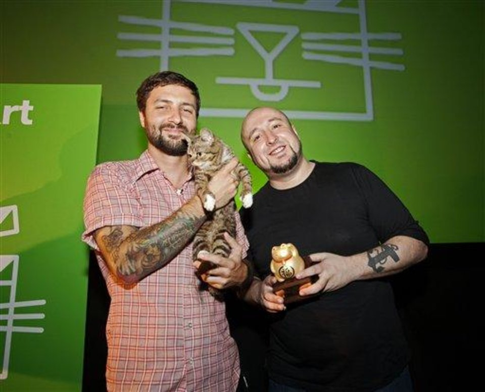 Photo - In this Aug. 30, 2012 publicity photo provided by the Walker Art Center, festival attendee, Mike Bridavsky and his cat Lil Bub, left, pose with Golden Kitty Award-winner William Braden, at the Walker Art Center Internet Cat Video Festival in Minneapolis. (AP Photo/Walker Art Center, Gene Pittman)