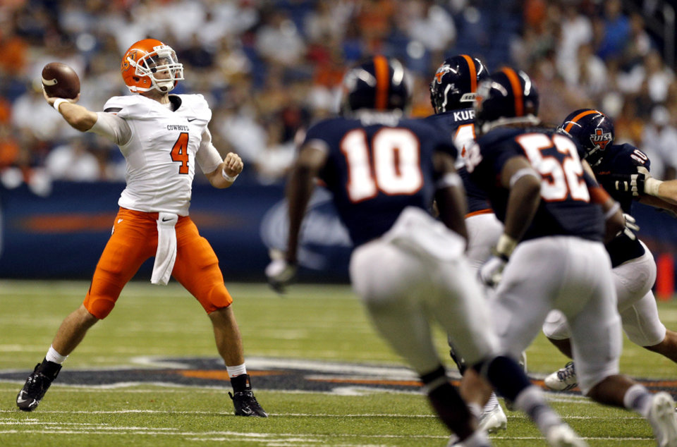 Photo - Oklahoma State's J.W. Walsh (4) throws a pass during a college football game between the University of Texas at San Antonio Roadrunners (UTSA) and the Oklahoma State University Cowboys (OSU) at the Alamodome in San Antonio, Saturday, Sept. 7, 2013.  Photo by Sarah Phipps, The Oklahoman