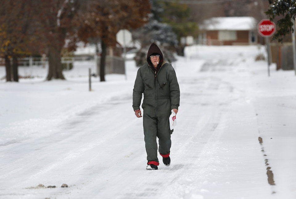 Photo - A man walks home after a trip to the drug store in Midwest City  on Friday,  Dec. 6, 2013. Photo by Jim Beckel, The Oklahoman