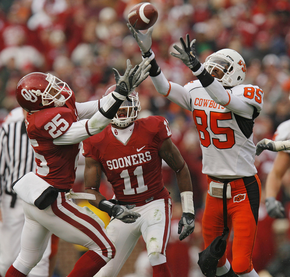 Oklahoma State's Damian Davis (85) pulls in a pass over Oklahoma's D.J. Wolfe (25) and Lendy Holmes (11) during the first half of the Bedlam college football game between the University of Oklahoma Sooners (OU) and the Oklahoma State University Cowboys (OSU) at the Gaylord Family -- Oklahoma Memorial Stadium on Saturday, Nov. 24, 2007, in Norman, Okla.   Photo By Nate Billings, The Oklahoman