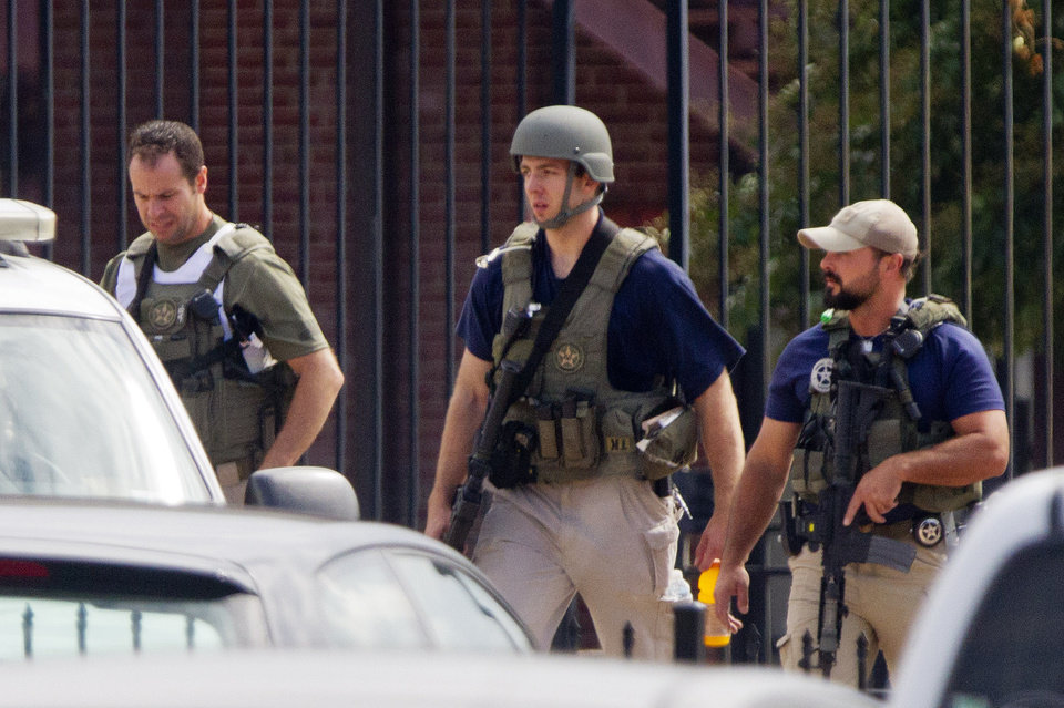 Photo - Armed U.S. Marshals leave the scene where a gunman was reported at the Washington Navy Yard in Washington, on Monday, Sept. 16, 2013. At least one gunman launched an attack inside the Washington Navy Yard, spraying gunfire on office workers in the cafeteria and in the hallways at the heavily secured military installation in the heart of the nation's capital, authorities said.  (AP Photo/Jacquelyn Martin)