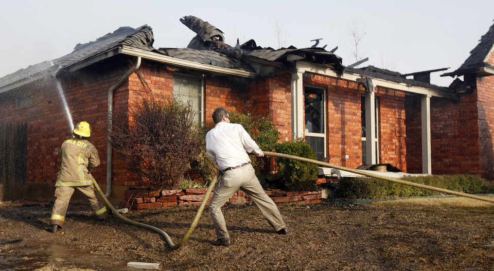 Photo - Paul Norwood helps a firefighter with a fire at a neighbor's home in the Oakwood East Royale neighborhood in Midwest City, Thursday, April 9, 2009. Photo by Bryan Terry, The Oklahoman