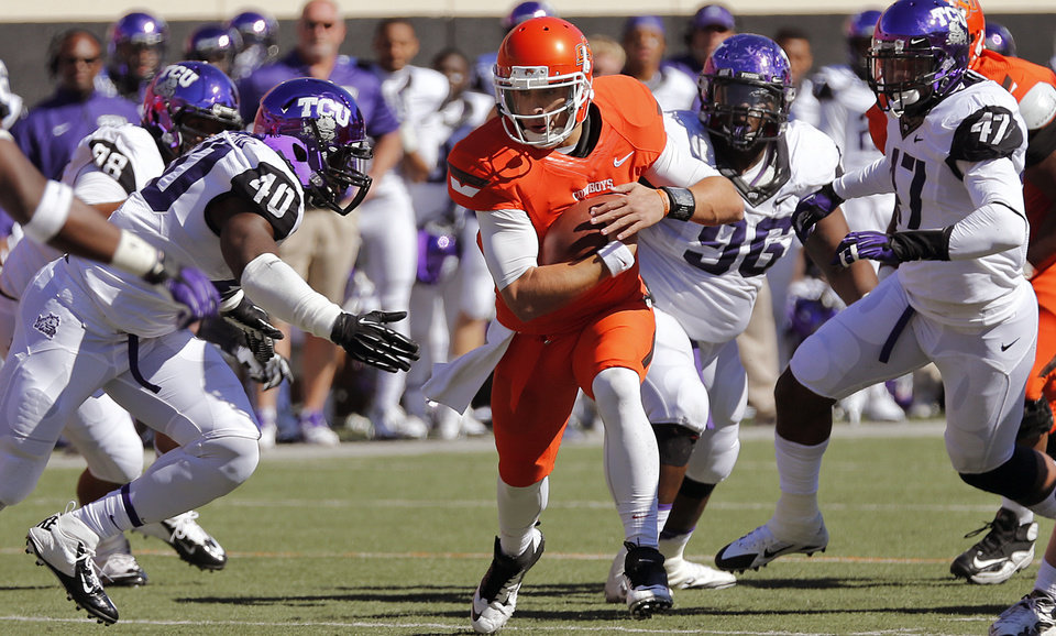 Oklahoma State\'s Clint Chelf (10) runs through the TCU defense during a college football game between the Oklahoma State University Cowboys (OSU) and the Texas Christian University Horned Frogs (TCU) at Boone Pickens Stadium in Stillwater, Okla., Saturday, Oct. 19, 2013. Photo by Chris Landsberger, The Oklahoman